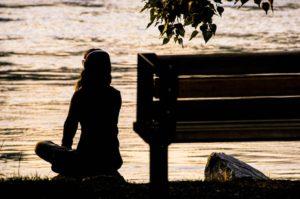 Mujer meditando al atardecer